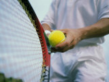 Man Holding a Tennis Ball And a Tennis Racket