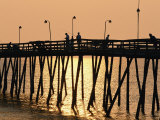 People on a Pier are Silhouetted at Twilight