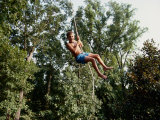 A Young Boy Takes a High Arc on a Rope Swing