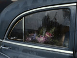 A Floral Arrangement Seen Through the Rain-Spattered Window of a Car
