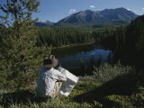 A Man with a Cowboy Hat Reads a Map and Gazes Across a River