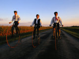 A Family  Dressed in Period Attire  Ride Old-Fashioned Bicycles Dating from the Late 1800s