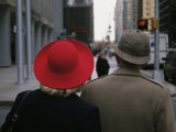 Rear View of Two People Wearing Hats Stopped at a Crosswalk
