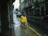 Two People Share a Raincoat as They Hurry Down a Rainy Street
