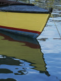 The Bow of an Anchored  Striped Boat is Reflected on the Water