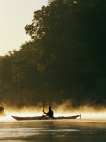 A Kayaker Paddles Through the Mist in the Low Sunlight