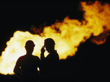 Natural Gas Workers Silhouetted by Burning Dross