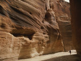 A Hiker is Dwarfed by the Sandstone Walls of a Utah Canyon