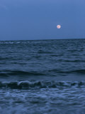 A Twilight Shot of Waves Coming into Shore with the Moon in the Background