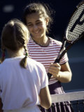 Two Girls Shaking Hands over the Net at a Tennis Court