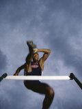 Low Angle View of a Young Man Jumping over a Hurdle