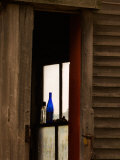 Old Blue Bottle in Window of Barn in Rural New England  Maine  USA