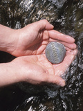 Person Holding Rock with the Word Blessings in Rushing Water