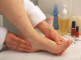 Woman Massaging Foot After Bath