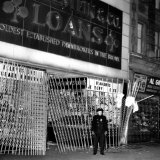A Policeman Stands in Front of a Pawn Shop