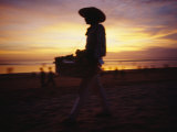 A Snack and Cigarette Vendor in a Straw Hat on the Beach at Dusk