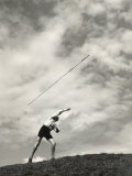 Young Boy Atop a Hill Hurls a Javelin into the Air