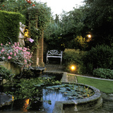 Garden Lighting Beside Italianate Pool & White Female Statue  Wrought Iron Bench