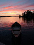 Canoe Floating in Lake During Sunset