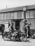Motor Cycle Rider Stops at a Garage in Scotland for Petrol Sitting