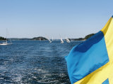 Swedish Flag with Sailboats in the Background  Stockholm Archipelago  Sweden