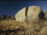 A Huge Boulder That is Split in Half Rests on a Grassy Knoll