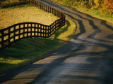 Twilight View of a Wooden Fence and its Shadow Along a Country Road