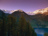Twilight View of a Small Lake Among Snow-Patched Mountains