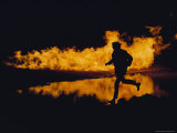 A Silhouetted Man Runs Past a Wall of Fire and its Reflection at Night