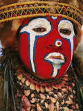 A Tribal Woman Clad with Shell Necklaces and Bright Face Paint