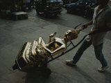 A Golden Buddha Statue is Wheeled by Handtruck on a Thai Street