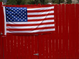 A United States Flag Hangs on a Bright Red Fence