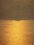 Sunlight on the Hooghly River and Mist Enshrouded Riverside Buildings