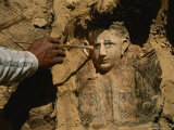 An Archeologist Brushes Dirt from the Mummy of a Child