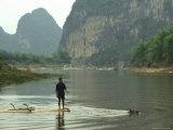 A Water Buffalo Pulls a Farmer on Bamboo Raft Across Mingjiang River