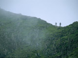 Hikers Climb a Fog-Shrouded Ridge on Mount Snowdon
