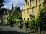 Hikers Jog Along a Street in the Village of Castle Coombe