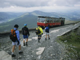A Train Filled with Tourists Passes Hikers Descending Mount Snowdon