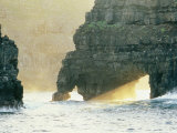 Sunlight Beaming Through Arches in Surf-Pounded Rock Formations