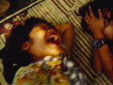 Two Young Girls Laugh Hysterically on a Bamboo Straw Mat in a Park