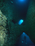 Diver Swimming Around Crevasses in a Reef Wall