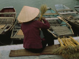 A Woman Makes a Straw Broom as She Awaits Tourists to Ride Her Boat  Hoa Lu