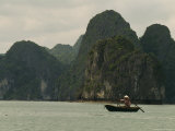 Woman in a Conical Hat Rows a Traditional Fishing Boat in Halong Bay