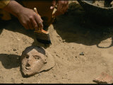 An Archeologist Brushes Sand Away from a Ceramic Artifact