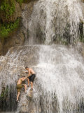 A Man Helps Another Climb onto a Waterfall