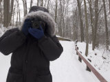 Man Bundled up in Parka Holding a Camera Ready to Take a Photograph