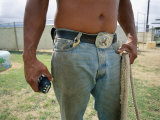 A Close View of a Man in Jeans with a Large Belt Buckle Holding a Rope