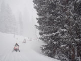 A Small Group of Snowmobilers Turn a Corner in a Snowstorm