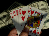 Hand Holding a Straight Flush in Front of Several Hundred Dollar Bills