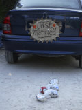 "A ""Just Married"" Sign and Tin Cans are Atached to the Back of a Car"